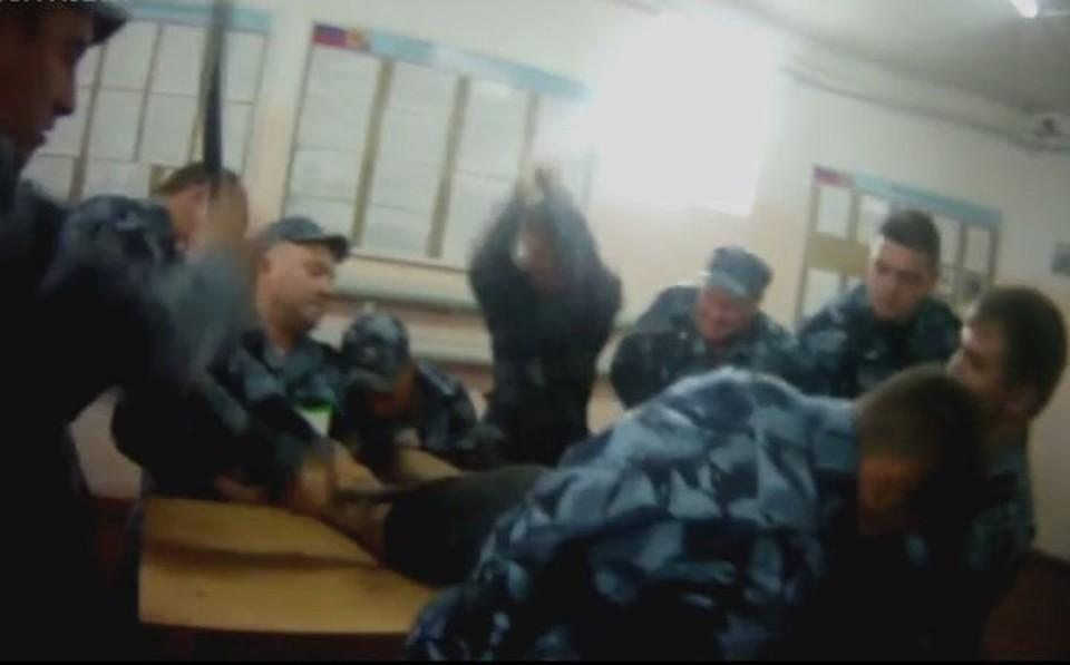 """Мужчину валят на парты, несколько человек его держат, несколько - бьют. Скриншот с видео фонда """"Общественный вердикт"""""""