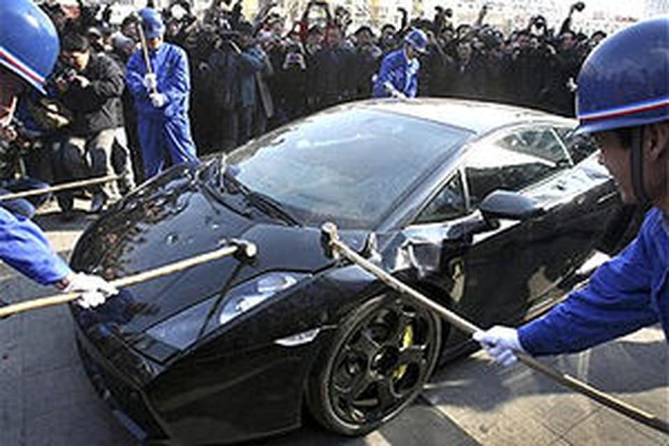 Рабочие с увлечением принялись крушить дорогой автомобиль